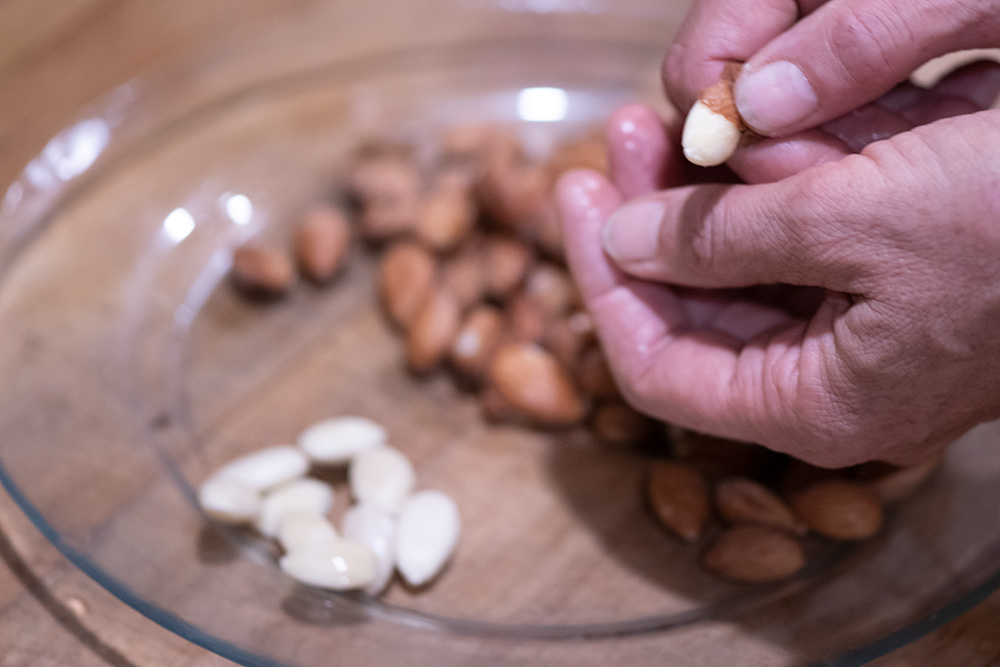 Removing skin from blanched almonds